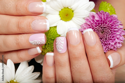 Staande foto Manicure Hands with french manicured nails and a bouquet of flowers