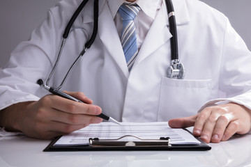 Close-up Of A Doctor Analyzing Report