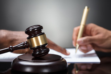 Gavel In Front Of Person's Hand Signing Legal Document