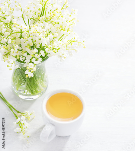 Fotobehang Lelietjes van dalen Bouquet of Lilies of the Valley and cup of tea on white wooden table.
