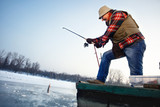 Fisherman draws hooked fish from frozen water - 189777153