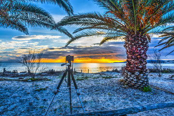 Dslr camera on a tripod by the sea