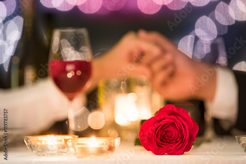 Date night. Man and woman holding hands. Love and dating concept. Focus on rose.  © kieferpix