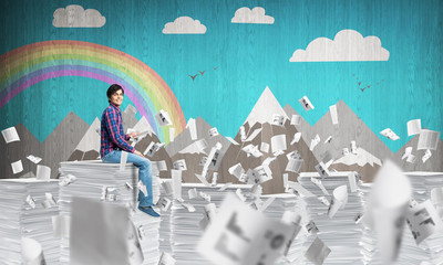 Young man sitting on pile of paper documents.