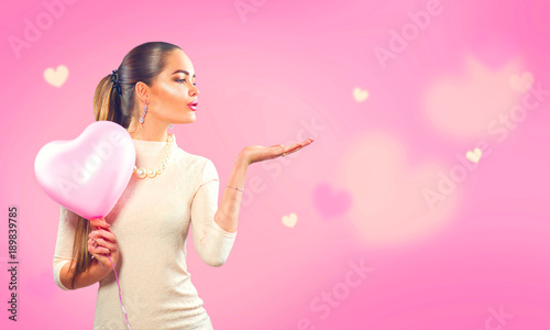 Valentine's day. Beauty girl with pink heart shaped air balloon pointing hand, blows hearts on pink background - 189839785