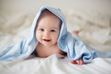 Fototapety Cute little baby boy, relaxing in bed after bath, smiling happily