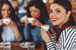 Quadro Three young women enjoy coffee at a coffee shop