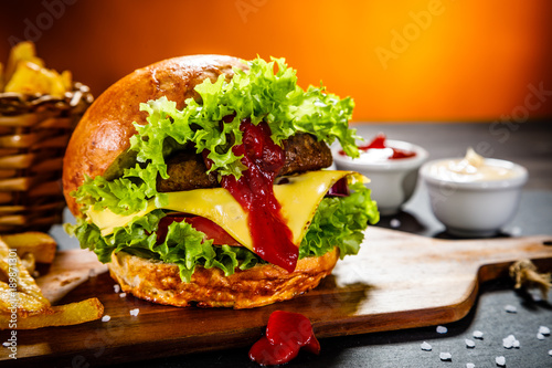 Tasty burger with chips served on cutting board  - 189871301