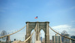 View of Brooklyn Bridge towers over blue sky with Manhattan skyline on background, in New York City
