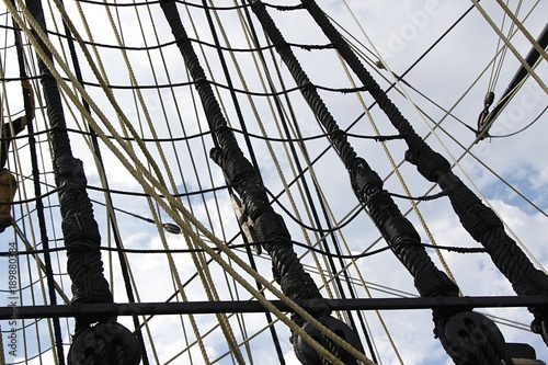 Foto op Plexiglas Schip Detail of mast of ship. Detailed rigging with sails. Vintage sailing ship block and tackle.