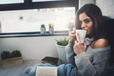Beautiful young woman at home drinking coffee reading a book