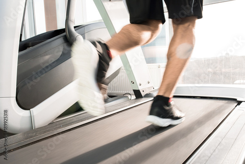 Wall mural Blurred motion of muscular  male legs running on treadmill lit by sunlight