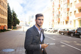 Young urban businessman professional on smartphone walking in street using mobile phone. - 189928772