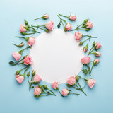 Flowers composition. Wreath made of pink rose flowers on blue background. Flat lay, top view, copy space.