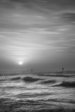 Beautiful dramatic black and white stormy landscape image of waves crashing onto beach at sunrise - 189931923