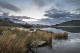 Stunning sunrise landscape image in Winter of Llyn Cwellyn in Snowdonia National Park with snow capped mountains in background - 189932377