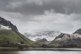 Beautiful Winter landscape image of Llyn Nantlle in Snowdonia National Park with snow capped mountains in background - 189932518