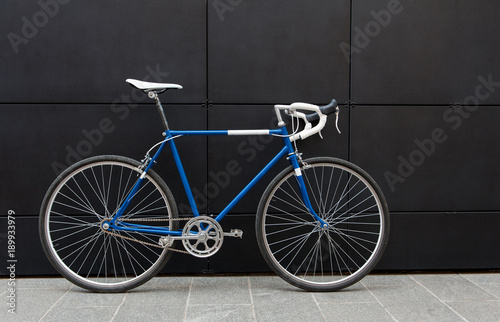 Foto op Canvas Fiets Vintage blue city bicycle against a black wall