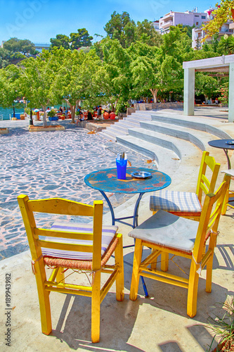sidewalk cafe with tables and yellow chairs, Crete, Greece