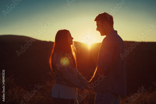 Young loving couple enjoys the sunset