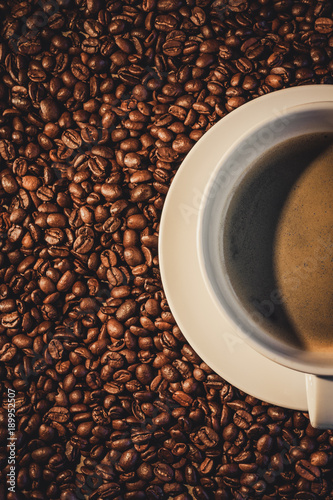 Poster Koffiebonen A half of a filled coffee cup with coffee beans from above