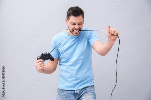 Angry man with video game controller on grey background