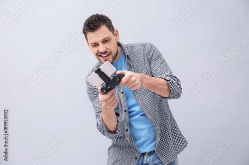 Emotional man with video game controller for smartphone on grey background