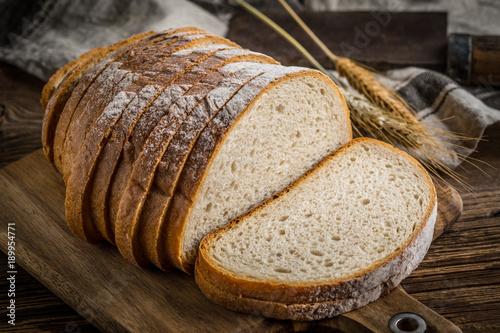 Fototapeta Sliced loaf of bread on a chopping board.