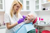 Senior man having dental treatment at dentist's office.