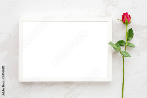 Valentine's day background, template, Red rose and blank white wooden frame on white marble background with copy space for text, flat lay
