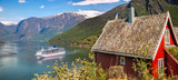 Red cottage against cruise ship in fjord, Flam, Norway - 189963981