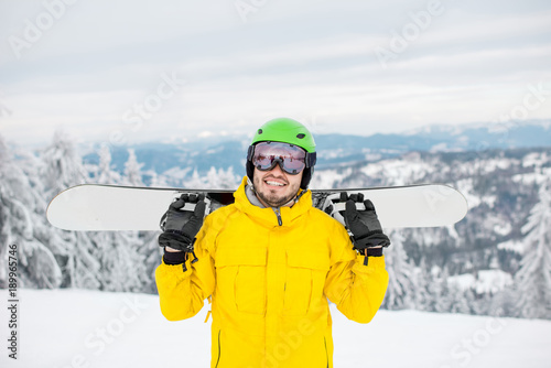fototapeta na ścianę Portrait of a man dressed in winter sports clothes holding a snowboard at the mountains