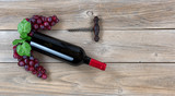 Red wine bottle with grapes and corkscrew on weathered wooden boards - 189972996