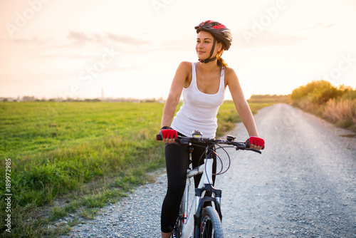 smiling girl on a bicycle outside the city at sunset