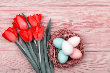 Easter Eggs in a birds nest with colorful tulips