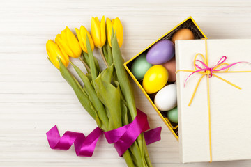Easter Eggs in a box with colorful yellow tulips