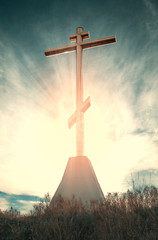 Dramatic filtered Christian cross with sun rays