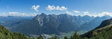 Panorama of an Austrian village in a valley. A few clouds in the sky on a sun filled day over an isolated town in the alps.