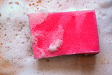 Pink sponge with white soap foam on wooden table - 189986314