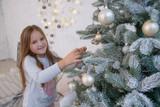 Girl decorating Christmas tree - 189996156
