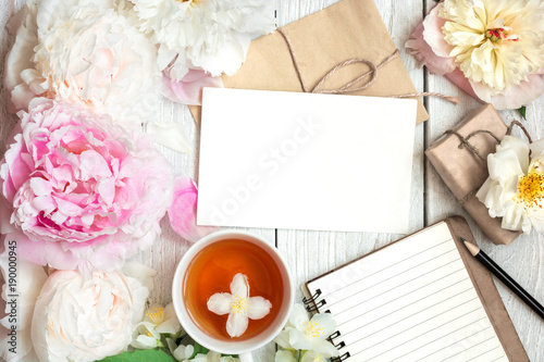 Creative layout made of peony, rose and jasmine flowers with cup of tea, blank greeting card, lined notebook