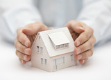 Property insurance. House miniature covered by hands. - 190005349