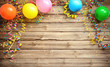 Leinwandbild Motiv Colorful carnival or party frame of balloons, streamers and confetti on rustic wooden board