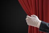Actor is pulling red curtains in theatre with hand. - 190020791
