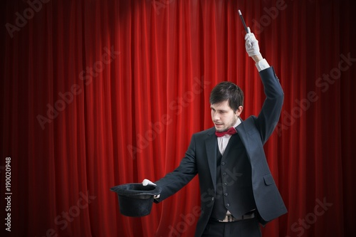 Happy magician or illusionist is showing magic trick with his wand. Red curtains in background.