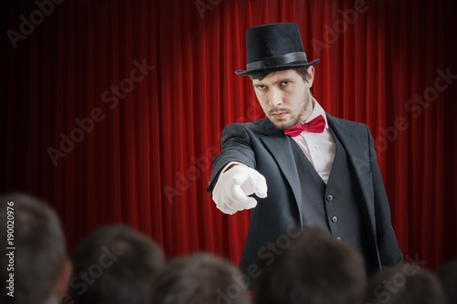 Young illusionist or magician is selecting volunteer from the audience.