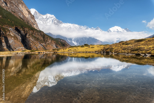 Tuinposter Canyon Majestic mountains with high rocks with snow covered peaks, mountain lake, beautiful reflection in water, blue sky with clouds in sunset. Nepal. Amazing tranquil landscape with mountains. Himalayas