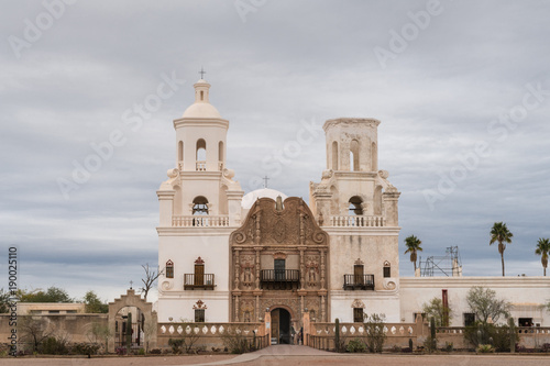 Foto op Canvas Arizona Tucson, Arizona, USA - January 9, 2018: White and brown front facade of Historic San Xavier Del Bac Mission under heavy gray, white cloud deck. Some greenish desert plants in front.