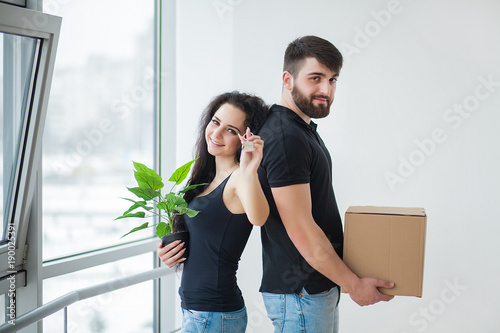 Young couple unpacking cardboard boxes at new home.Moving house.