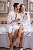 Young couple in luxury spa tasting glass of white wine - 190029578